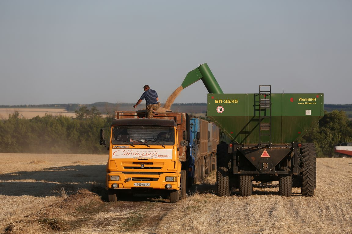 """A Kamaz PJSC truck Acros combine harvesters, manufactured by Rostselmash OJSC, during the summer wheat harvest on a farm operated by 'Svetlyi"""" Group of Companies, in Kamenka village, outside Rostov, Russia, July 5, 2019. http://gk-svetlyi.ru/"""