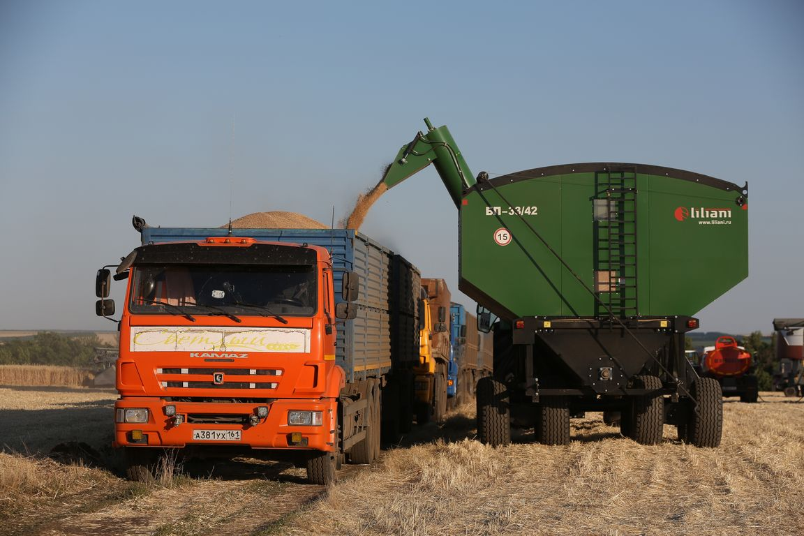 """A Kamaz PJSC truck. Acros combine harvesters, manufactured by Rostselmash OJSC, during the summer wheat harvest on a farm operated by 'Svetlyi"""" Group of Companies, in Kamenka village, outside Rostov, Russia, July 5, 2019. http://gk-svetlyi.ru/"""