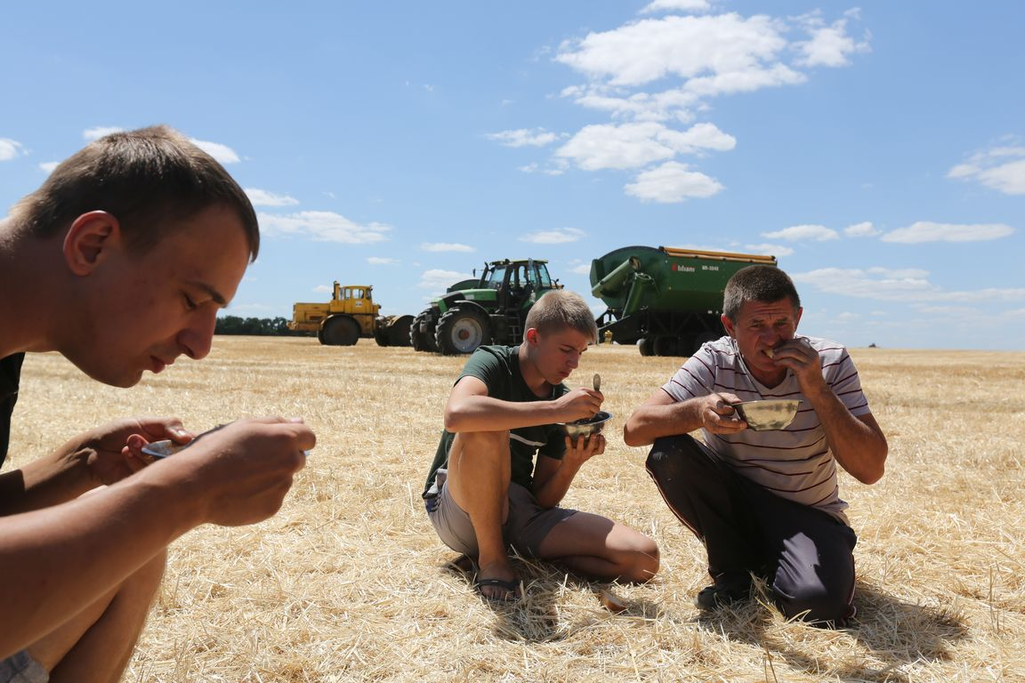 """Lunchtime. Acros combine harvesters, manufactured by Rostselmash OJSC, during the summer wheat harvest on a farm operated by 'Svetlyi"""" Group of Companies, in Kamenka village, outside Rostov, Russia, July 5, 2019. http://gk-svetlyi.ru/"""
